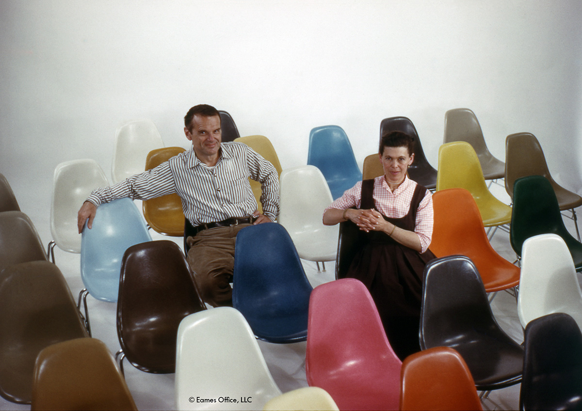 Charles & Ray Eames sitting on colourful shell chairs