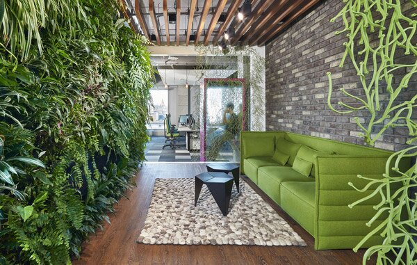 Green Vitra Alcove sofa opposite a living wall