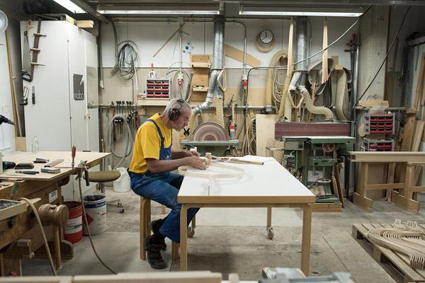 a man sat at a desk making something inside the artek factory