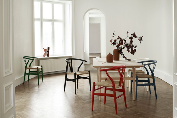 5 colourful CH24 Wishbone chairs surrounding a wooden dining table