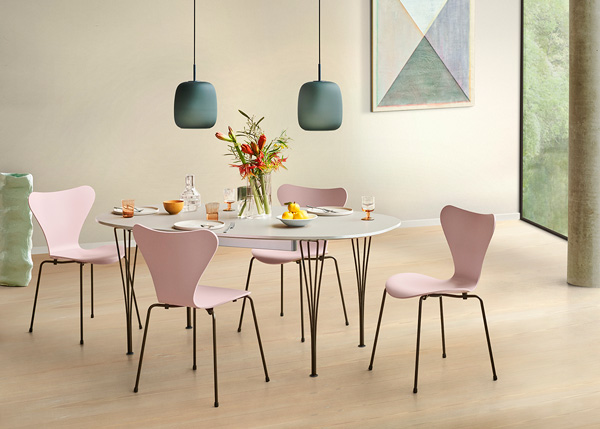4 pink Series 7 Chairs surrounding a white dining table