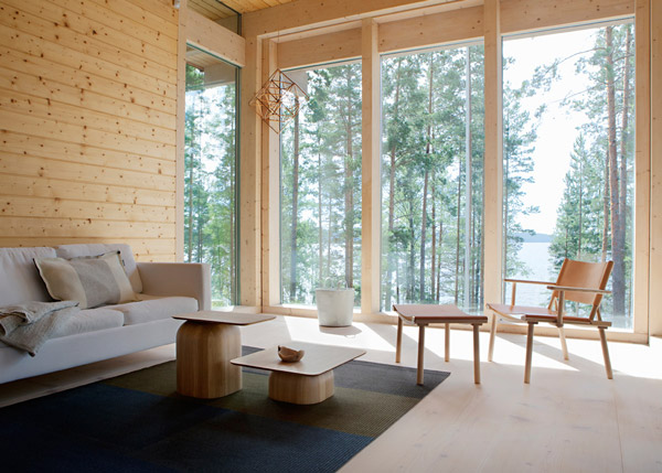 A timber interior with windows looking out at forest featuring designs from Nikari