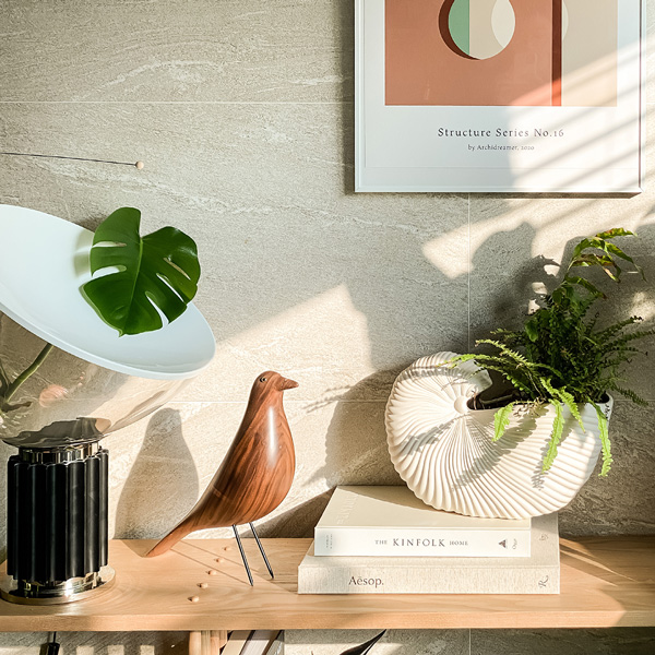 A Flos Taccia lamp, Vitra Eames House Bird and Ferm Living Shell Pot on a sideboard