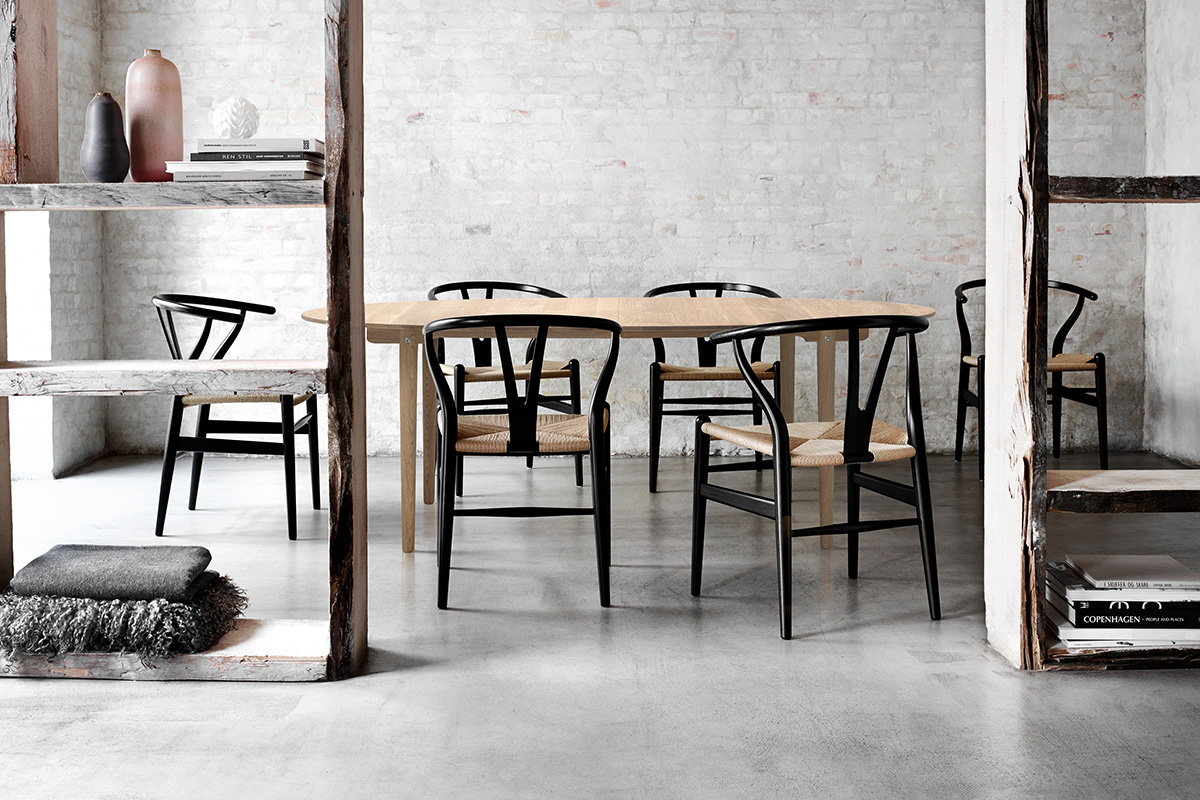 Set of 6 Carl Hansen CH24 Chairs with black painted frames around a dining table