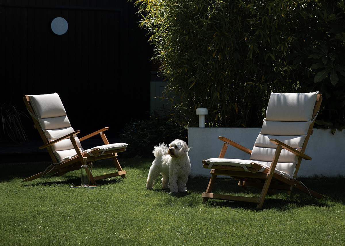 2 Carl Hansen & Son BM5568 Deck Chairs with a white dog standing in between