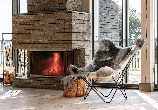 Cuero Design sheepskin butterfly chair iceland mariposa natural grey by a fireplace