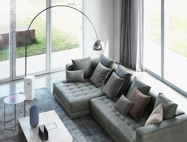 Flos Arco Floor Lamp hangs over corner sofa in grey minimal Italian living space