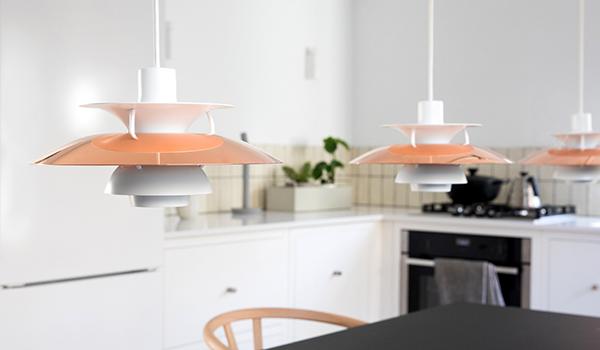 A row of 3 Louis Poulsen PH5 pendants in copper in a kitchen