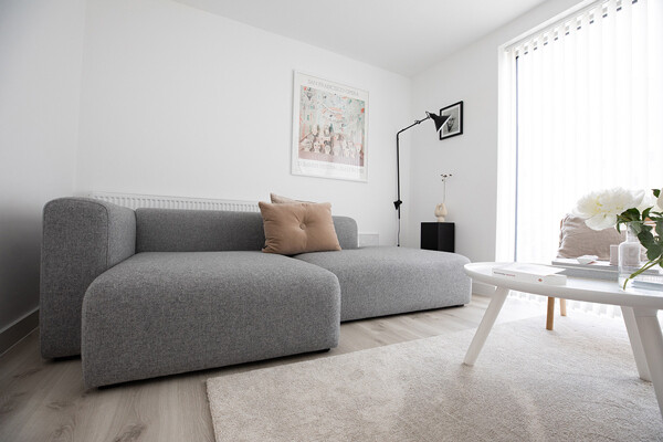 Minimal living room with the HAY Mags sofa and DCW wall light