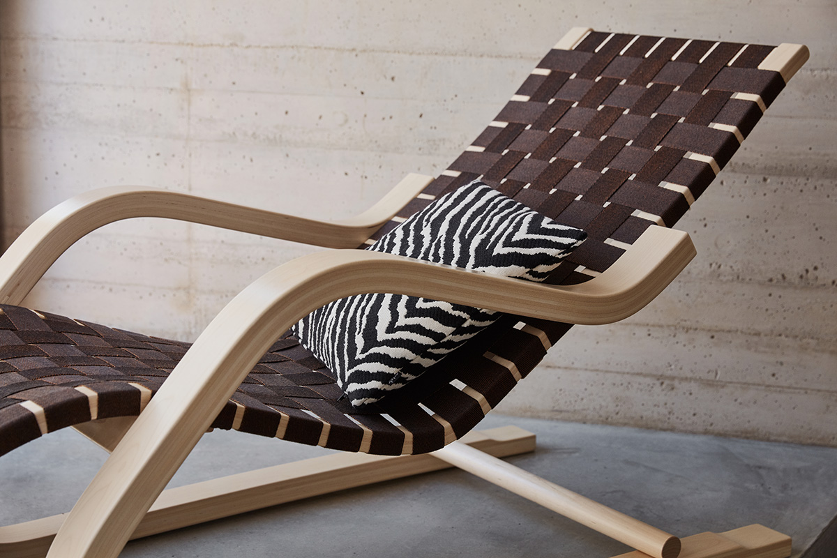 A close up shot of an Artek 43 Lounge Chair, with a wooden frame and webbed seat