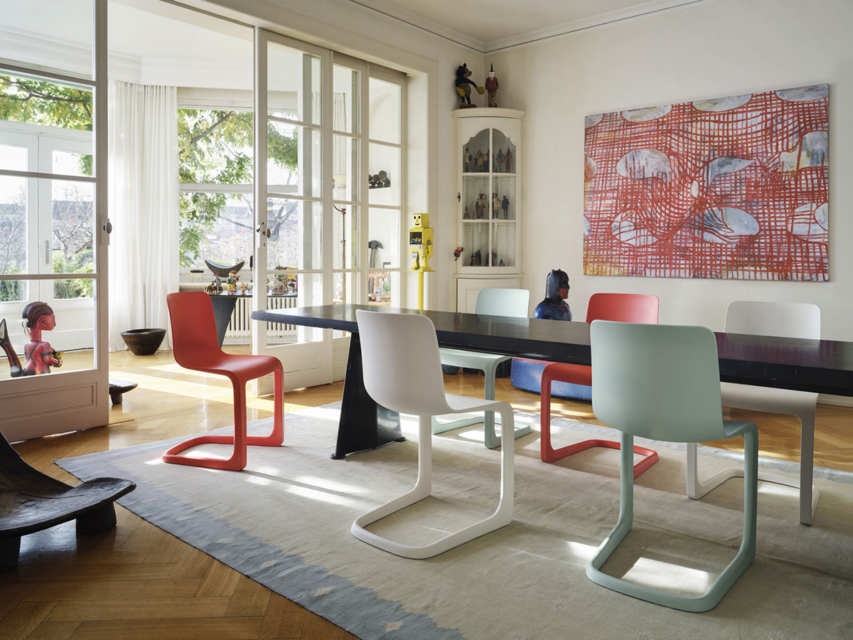 6 Vitra EVO-C chairs around a large dining table in a light filled home