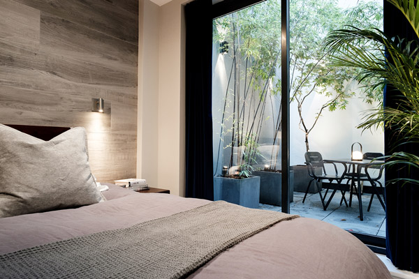 Looking out to an external courtyard from inside a modern bedroom