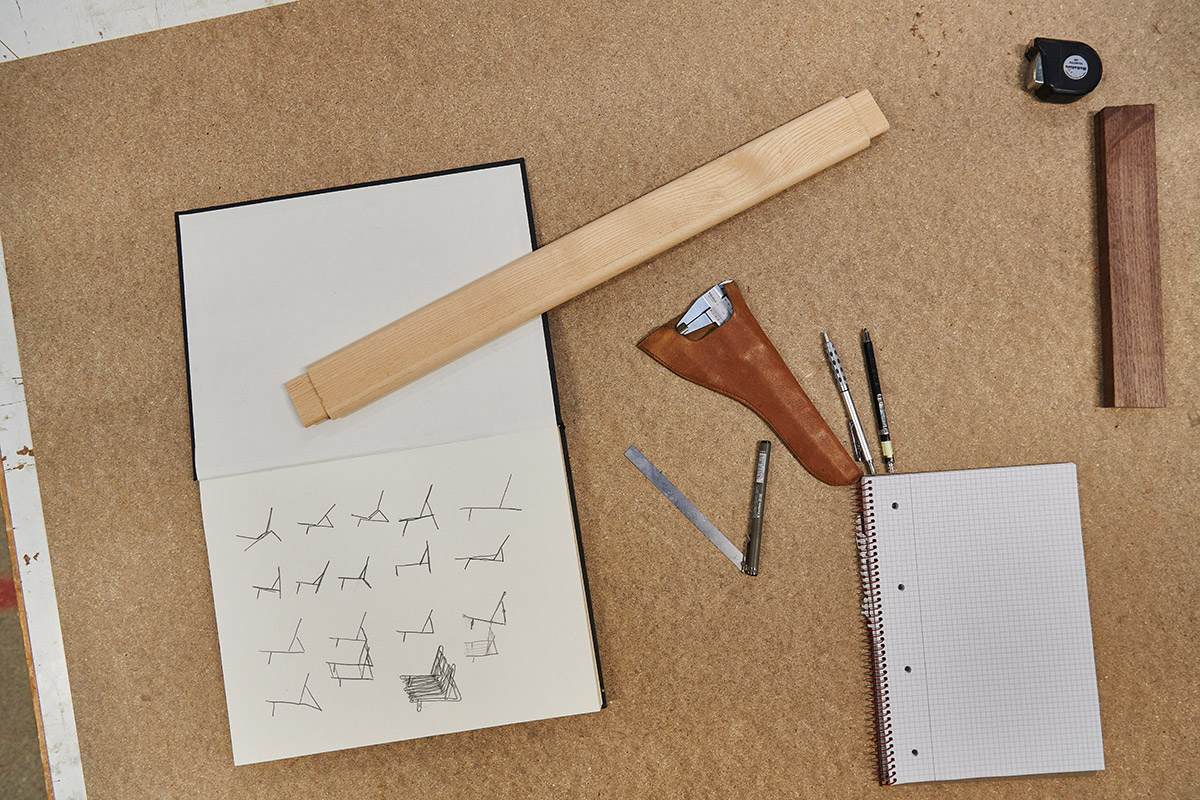 Sketches of the Gubi MR01 Initial Chair alongside pens on a woodworking bench