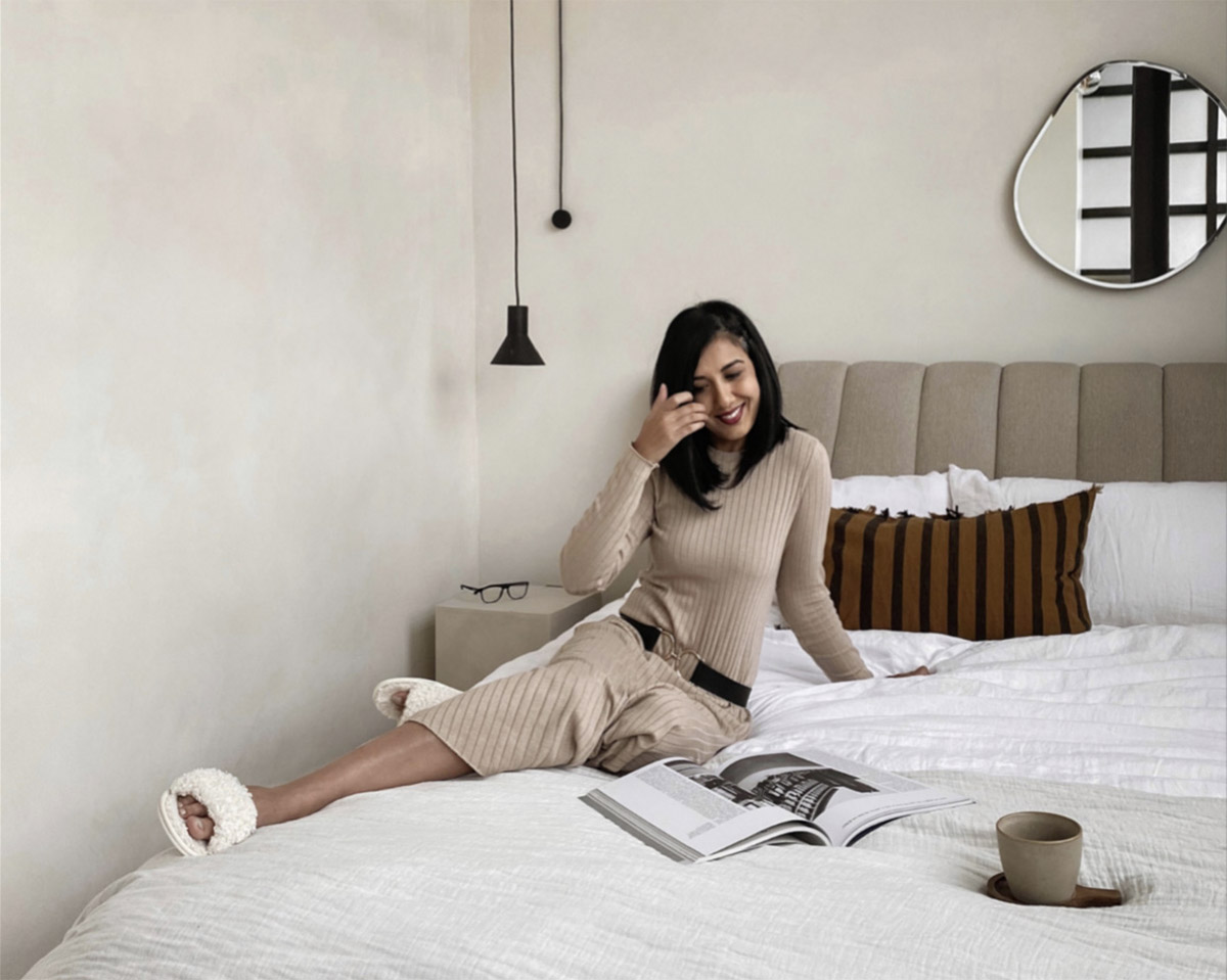 Lisa Mistry of Loft208 sitting on her bed with a magazine and coffee