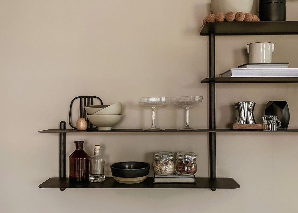 Asymmetrical wall shelves holding bowls, jars and cocktail glasses