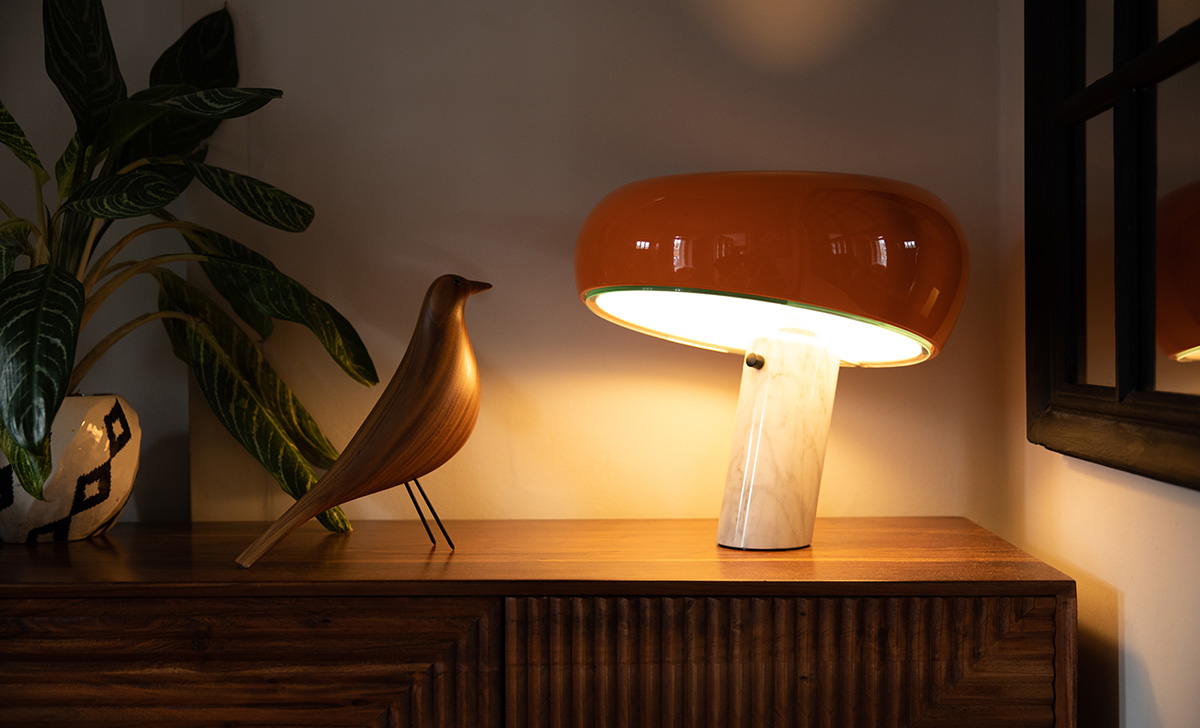 Orange Flos Snoopy Table Lamp and a Vitra Eames House Bird on a sideboard