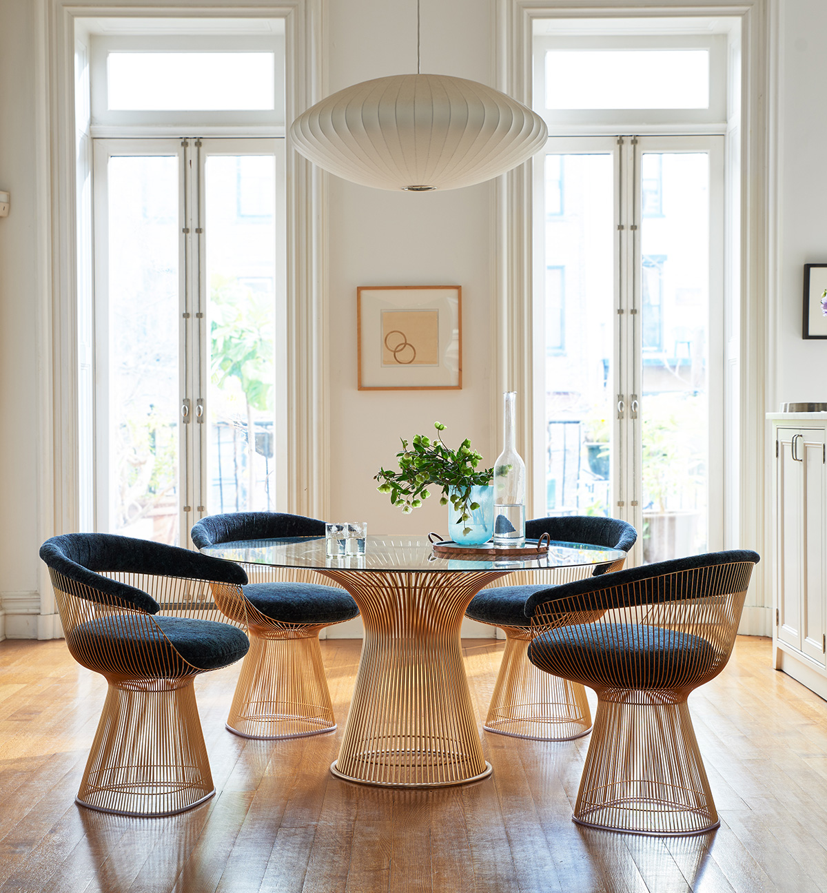 A dining room featuring A Knoll Platner Dining Table and Chairs and a Herman Miller Bubble Pendant