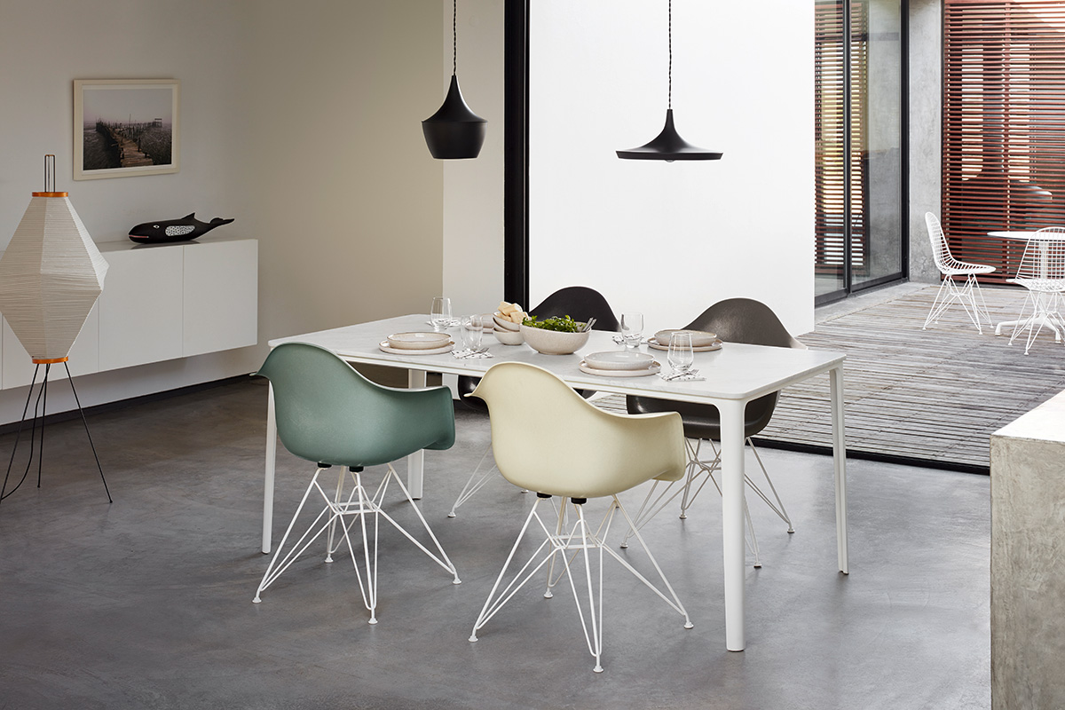 A modern dining set up featuring Eames Shell Chairs and Tom Dixon beat lights
