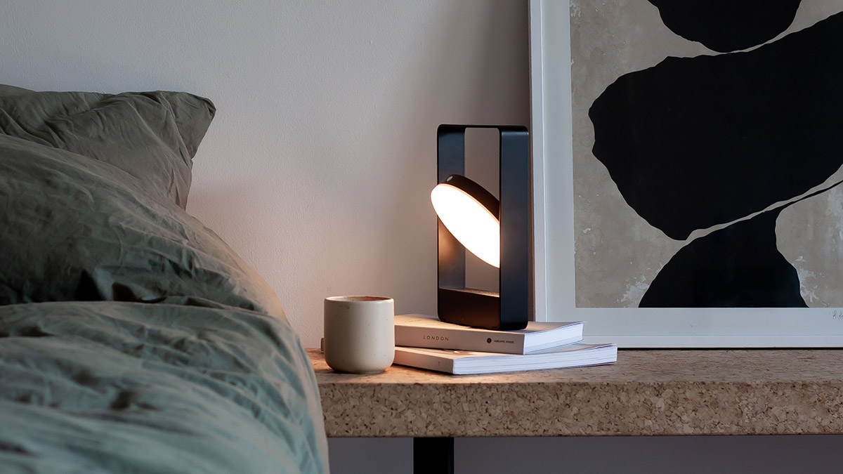 Case Mouro Portable Table Lamp on a cork bench next to a bed