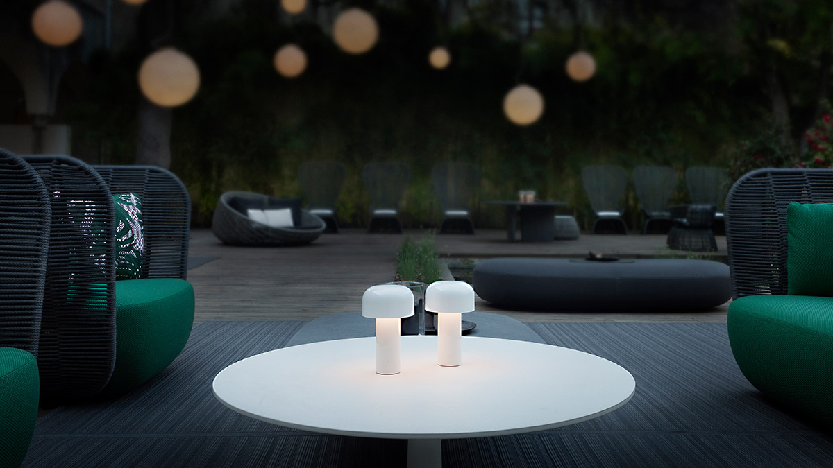 2 white Flos Bellhop lights on a garden table surround by green garden chairs