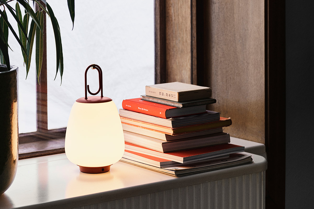 &Tradition Lucca Portable Table Lamp on a windowsill next to a pile of books
