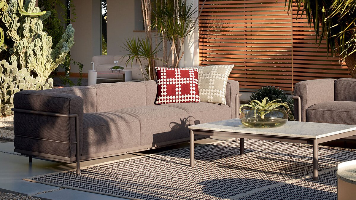 An outdoor living room with grey sofa and Cassina LC10-P Coffee Table