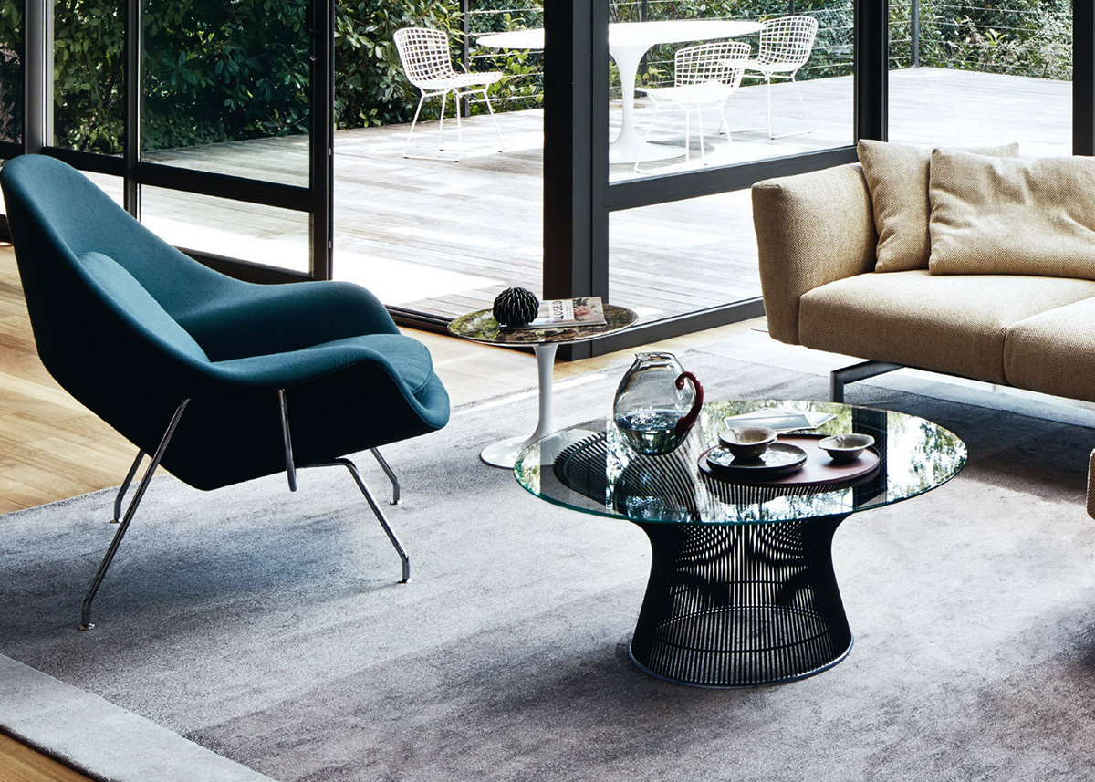 A modern living room featuring the Knoll Womb Chair and Platner Coffee Table