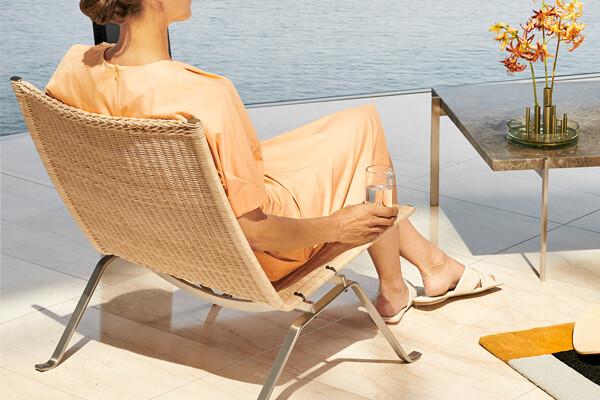 Woman sat in the Fritz Hansen PK22 Lounge Chair